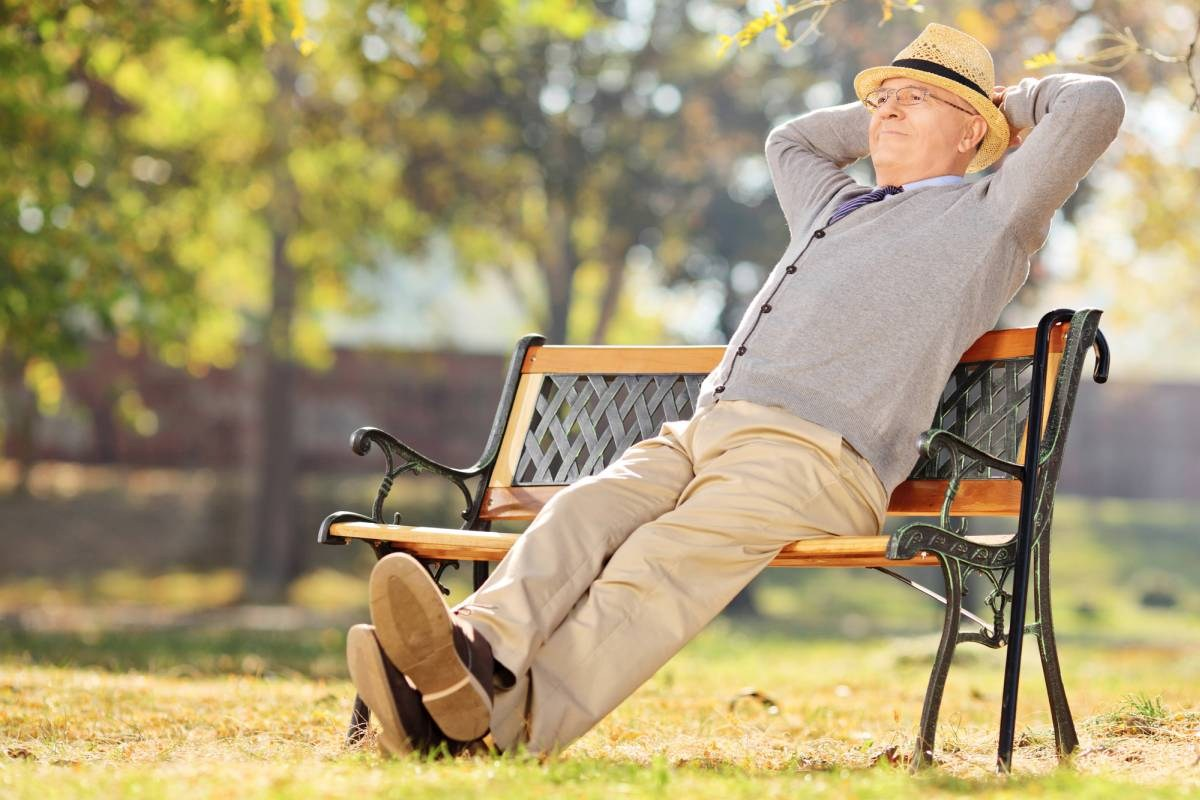 Relaxed Pensioner Sitting On Bench In Park